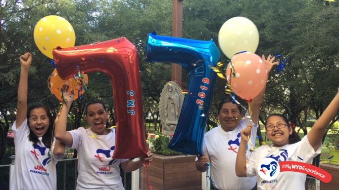 """A foto mostra o mexicano Pedro Cortés e sua esposa Martiza ao centro segurando balões em vermelho e azul com o número sete onde está escrito """"JMJ"""" e """"2019"""". Em referência a sétima participação de Pedro em Jornadas. Ao lado deles aparecem as duas filhos do casal também segurando balões em amarelo e laranja.. Eles vestem camisas da JMJ Panamá 2019 e comemoram a oportunidade de participar do evento."""