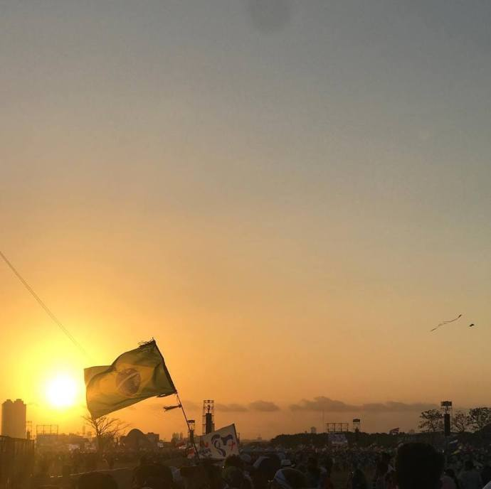 A foto mostra uma bandeira do Brasil em frente ao pôr-do-sol e milhares de jovens que participaram do evento.