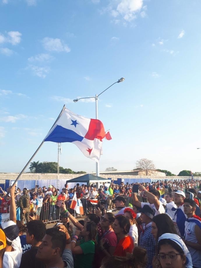 A foto mostra muitos jovens da Jornada Mundial da Juventude no Panamá e um vão no centro como corredor para a passagem do papa móvel. Um dos jovens na multidão segura uma bandeira tremulante do Panamá que se destaca ao fundo de um céu azul.