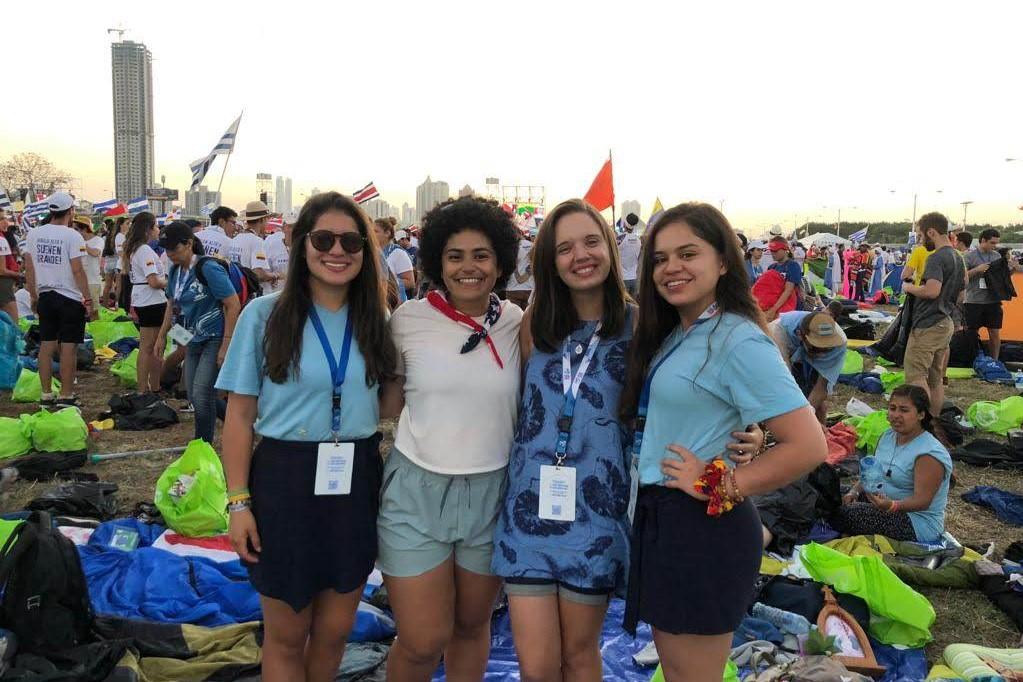 A foto apresenta Rebeca no centro de blusa azul com detalhes e azul escuro com o crachá da JMJ. Ao seu lado direito outras duas jovens e ao lado esquerdo outra jovem. Ao fundo muitos peregrinos da JMJ no Panamá com bandeiras.