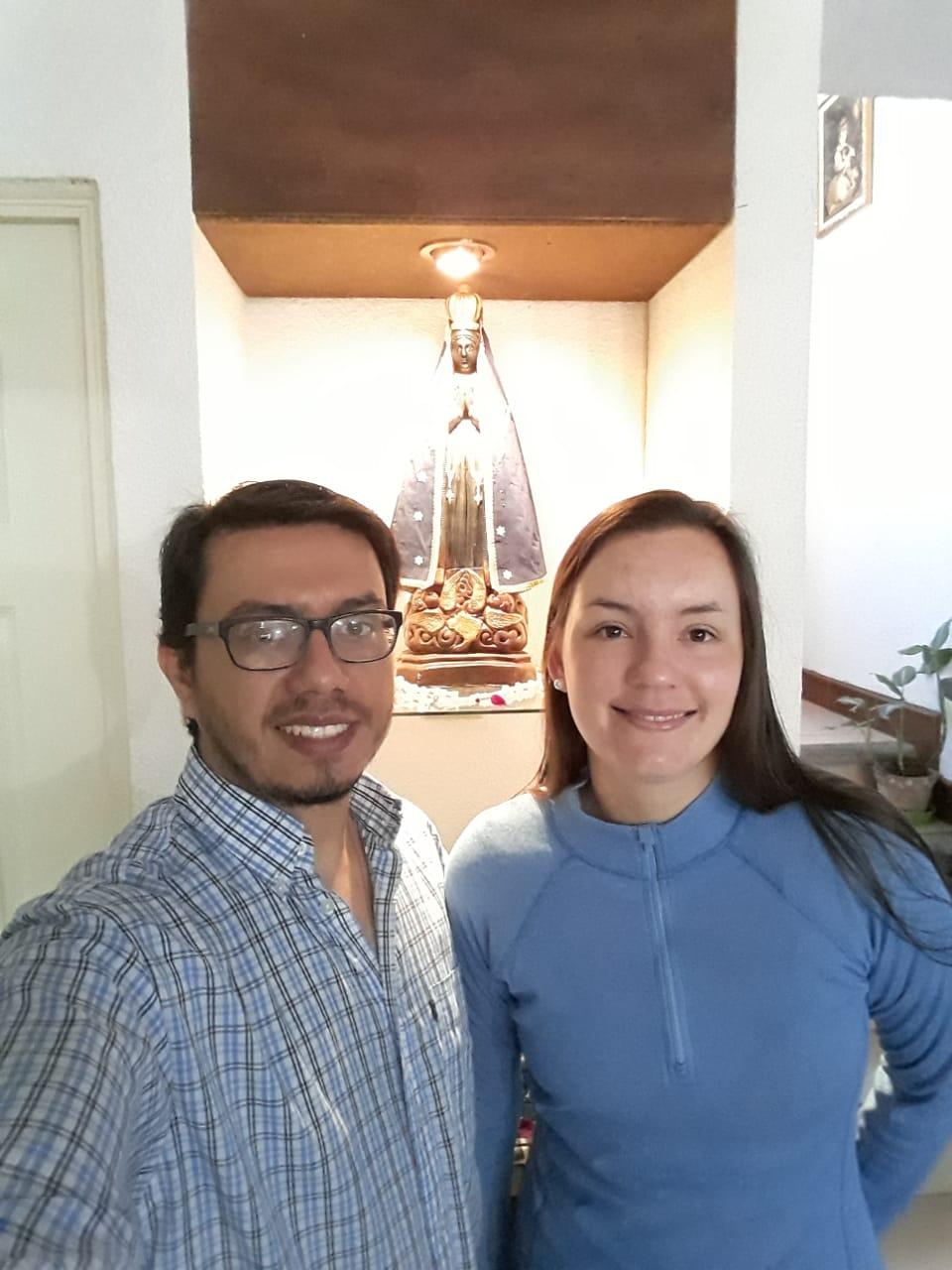 A foto mostra Milton de camisa litrada e Soledad de blusa azul sorrido. Ao fundo, uma imagem de Nossa Senhora Aparecida.