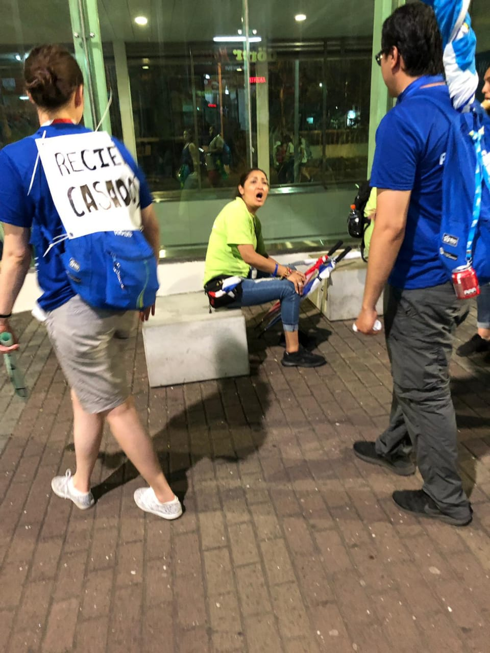 """A foto mostra o casal Soledad e Milton de costas com camisetas azuis e a mochila azul da JMJ no Rio. Soledad tem na costas um cartaz escrito """"recién casados""""."""