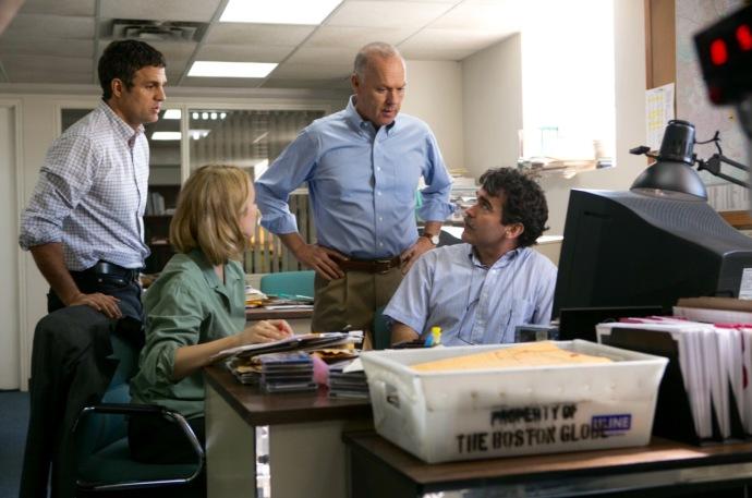 A imagem mostra os três repórteres na redação do jornal olhando para o editor. Dois estão sentados e um de pé ao lado do editor da equipe. Na imagem se vê muitos documentos, um computador e papéis sobre algumas mesas.
