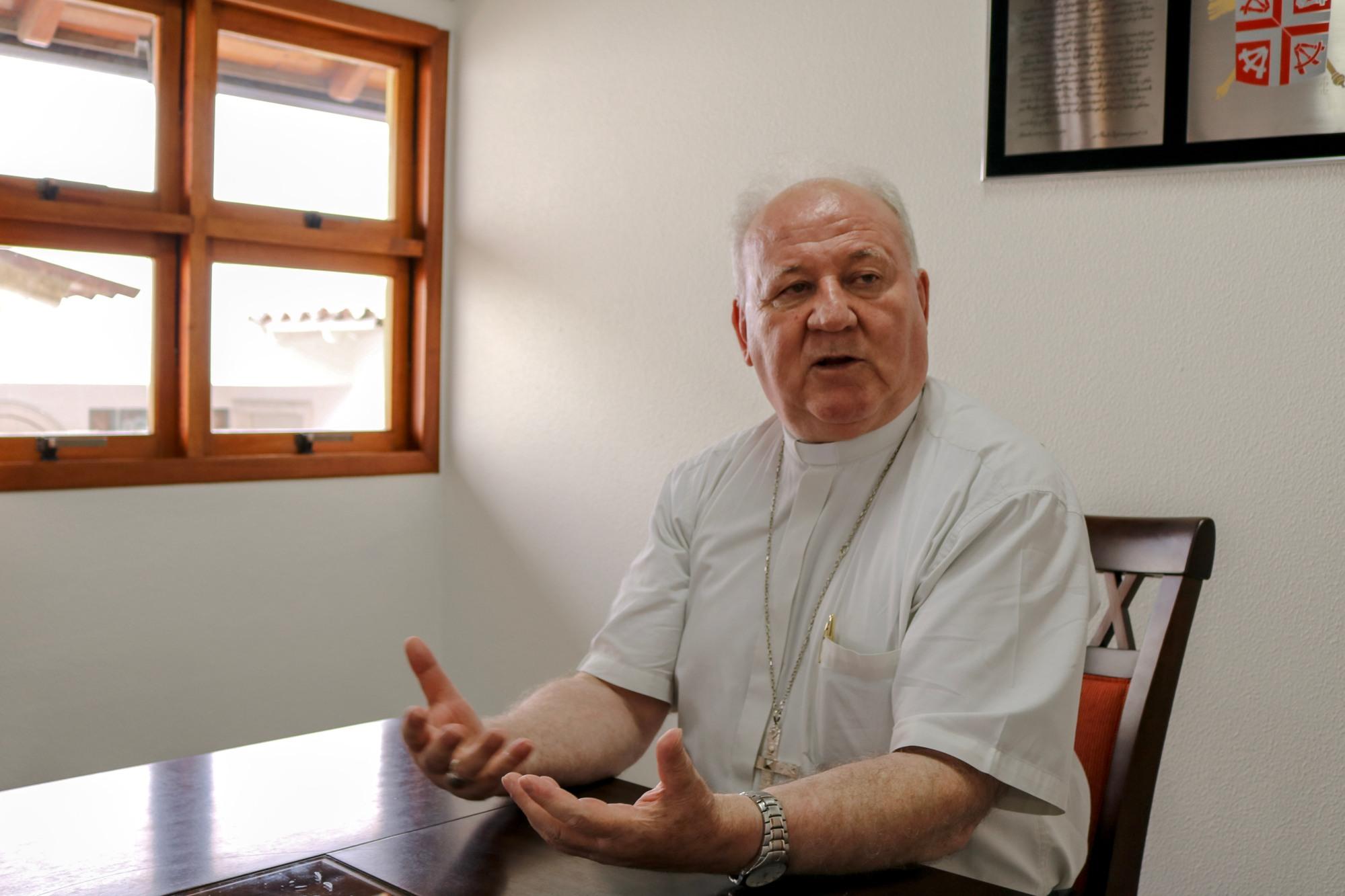 O bispo está de camisa de clerygman cinza e cruz peitoral sentado à mesa. Ele olha para a esquerda com as mãos abertas enquanto fala. Ao fundo uma janela deixa entrar a luz na sala de reuniões.