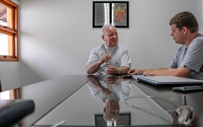 Na foto o bispo e o entrevistador parecem na ponta da mesa. No centro está Dom Wilson, olhando para o jornalista que está à direita.