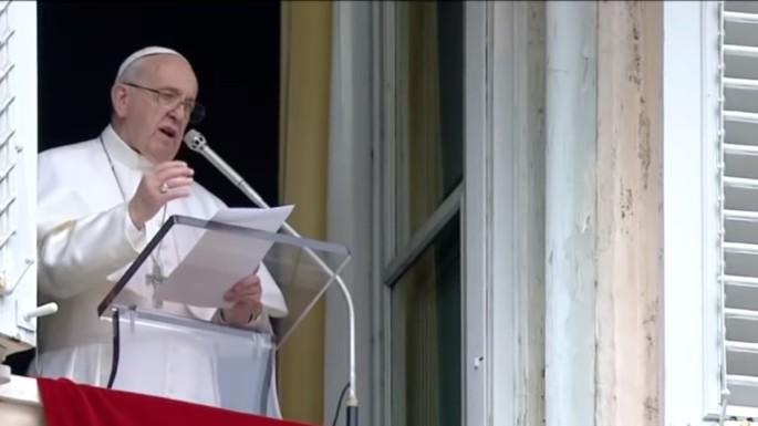 A imagem mostra o papa de branco com a mão direita levantada enquanto fala ao microfone na sacada do apartamento pontifício.
