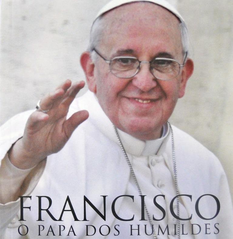 """A imagem é um recorte da capa do livro com a imagem do Papa Francisco sorrindo e acenando com a mão direita. A baixo está escrito o título do livro """"Francisco o papa dos humildes"""""""