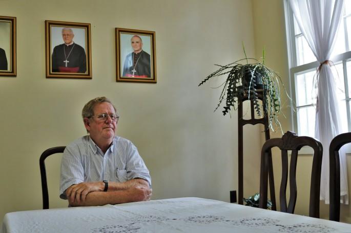 Na foto Dom Guilherme está sentado à mesa com os braços cruzados sobre ela. Ele olha em diagonal para a frente. Atrás dele, na parede, estão os quadros de seus antecessores.