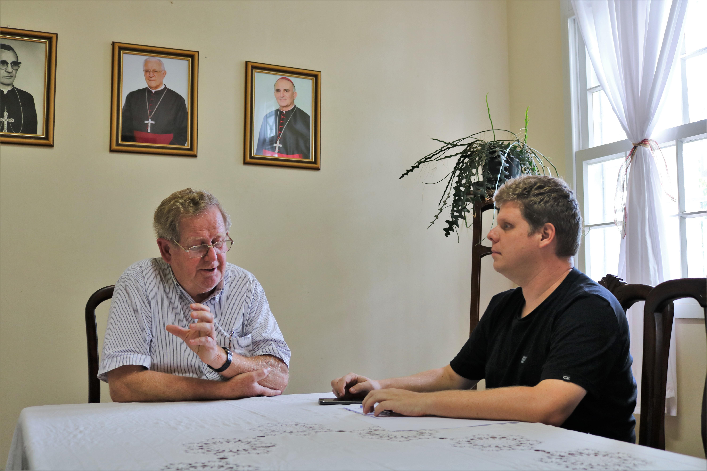 Na foto Dom Guilherme gesticula durante a entrevista. Ao lado, está o jornalista Thiago Caminada com os braços sobre a mesa.