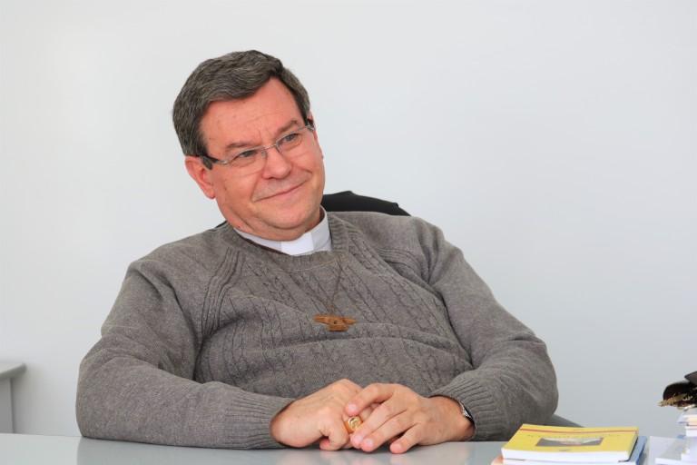Na foto, Dom Frei Severino está sentado à mesa com as mãos postas.